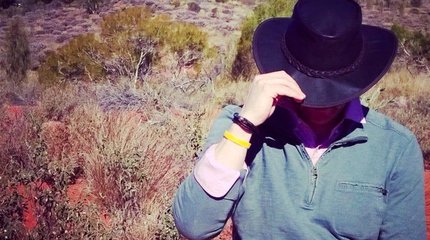 Man-tipping-hat-uluru-in-background
