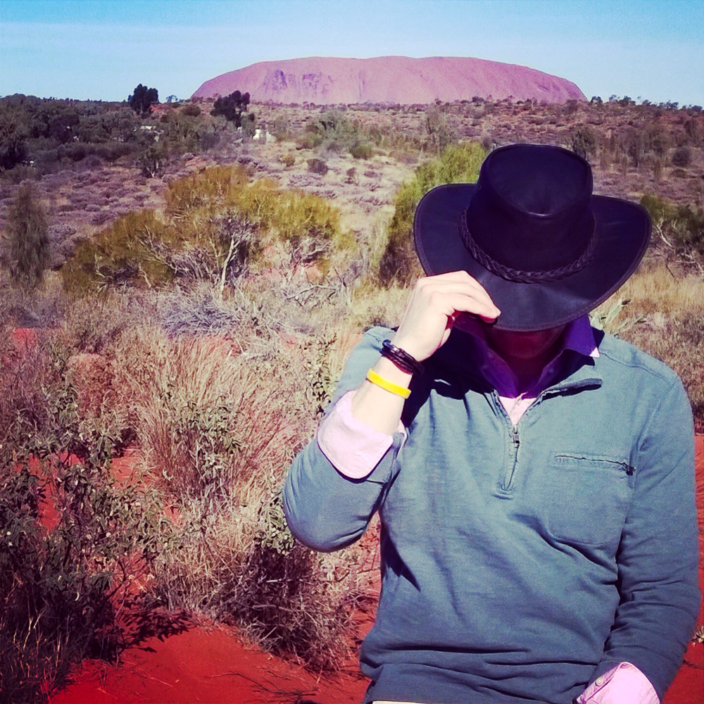 Man-tipping-hat-uluru-in-background