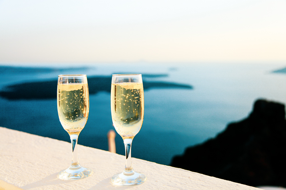 two-champagne-glasses-overlooking-blue-water